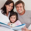 Smiling parents reading a story to their daughter — Stock Photo #11210998