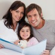 Portrait of parents reading a story to their daughter — Stock Photo #11211000