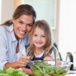 Portrait of a mother and her daughter preparing a salad - Stock Photo