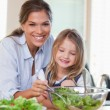Stock Photo: Portrait of a young mother and her daughter preparing a salad