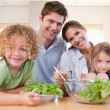 Smiling family preparing a salad together — Stock Photo