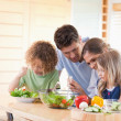 Family preparing a salad together — Stock Photo #11211187