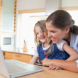 Smiling mother and her daughter using a laptop — Stock Photo #11211209