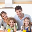 Smiling family having breakfast — Stock Photo #11211247