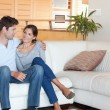 Smiling couple sitting on a couch — Stockfoto