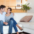Foto Stock: Smiling couple sitting on a couch