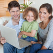 Stock Photo: Happy family using a laptop