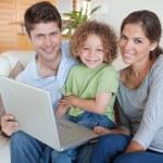 Happy family using a laptop — Stock Photo