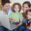 Smiling family using a laptop — Stock Photo #11211279
