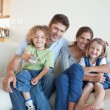 Smiling family watching TV together — Stock Photo #11211297