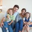 Portrait of a happy family watching TV together - Foto Stock