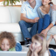 Portrait of parents watching their children using a laptop - Stock Photo