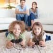 Children playing video games while their parents are watching — Stock Photo #11211329