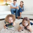 Cute children playing video games while their parents are watchi — Stock Photo