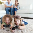 Portrait of children playing video games while their parents are — Stock Photo