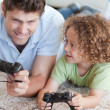 Stock Photo: Boy and his father playing video games