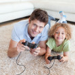 Stock Photo: Smiling boy and his father playing video games