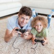 Stock Photo: Portrait of boy and his father playing video games