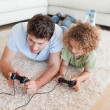 Stock Photo: Focused boy and his father playing video games