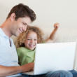 Cheerful boy and his father using a laptop — Stock Photo #11211350