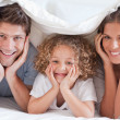 Family posing under a duvet — Stock Photo