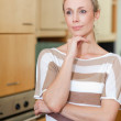 Woman in thoughts standing in kitchen - Stock Photo
