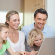 Family using laptop in the kitchen — Stock Photo