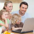 Family using the internet in the kitchen — Stock Photo
