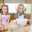 Stock Photo: Smiling siblings preparing dough