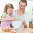 Smiling mother and daughter preparing dough for cookies — Stock Photo #11211547