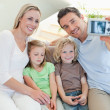 Man taking family picture on couch - Stock Photo