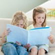 Siblings reading magazine on the sofa — Stock Photo #11211662