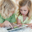 Siblings on the floor using tablet — Stock Photo