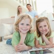 Children on the carpet with tablet and parents behind them — Stock Photo