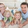 Stock Photo: Family lying on carpet