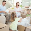 Stock Photo: Family unpacking cardboard box in living room