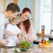 Couple letting their child stir the salad — Stock Photo