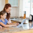 Mother and daughter with laptop in the kitchen - Stock Photo