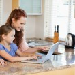 Mother and daughter with laptop behind the kitchen counter - Stock Photo