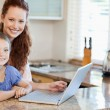 Mother and daughter surfing the internet in the kitchen - Stock Photo