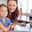 Stock Photo: Mother and daughter with notebook in kitchen