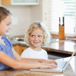 Siblings on the notebook in the kitchen — Stock Photo