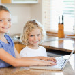 Smiling siblings on the laptop in the kitchen — Stock Photo