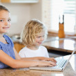 Siblings with laptop behind the kitchen counter — Stock Photo