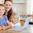 Stock Photo: Mother with children on them laptop in kitchen