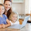 Mother with children on them laptop in the kitchen - Stock Photo