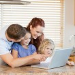 Family with laptop in the kitchen - Stock Photo