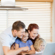 Family exploring the internet in the kitchen — Stock Photo