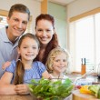 Stock Photo: Family standing behind the kitchen counter