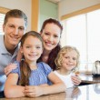 Stock Photo: Family standing together behind kitchen counter